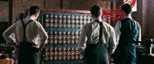 Alan Turing and team members at Bletchley Park, with a forerunner of the modern computer-- technology invented by brilliant people to break the Nazi Enigma encryption. Screenshot from official trailer, under fair use.